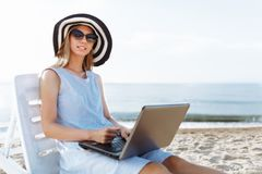 Beautiful girl sitting with a laptop on a chaise longue, a woman working on vacation, job search royalty free stock photos