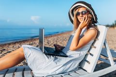 Beautiful girl sitting with a laptop on a chaise longue, a woman working on vacation, job search, talking on the phone royalty free stock photos
