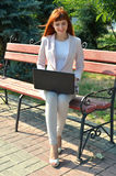 Beautiful girl sitting with a laptop. Red-haired girl on the old bench in the park with a laptop Royalty Free Stock Images