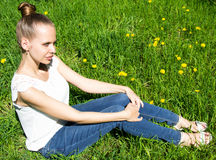 Beautiful girl sitting on the lawn with a dandelion Royalty Free Stock Image