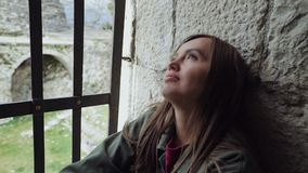 Beautiful girl is sitting locked up by the window with bars and sad. A beautiful girl is sitting locked up by the window with bars and sad stock video footage
