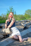 Beautiful Girl sitting on a log at the beach stock images