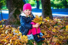 Beautiful girl sitting with maple leaves in autumn park Royalty Free Stock Photo