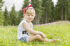Beautiful girl sitting on the meadow Stock Photo