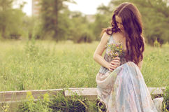 Beautiful girl sitting in the meadow. Beautiful girl sits with a bouquet of flowers in the meadow royalty free stock photos