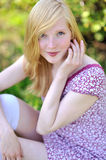 Beautiful girl sitting in a meadow and smiling to you - close up Royalty Free Stock Photos