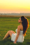 Beautiful girl sitting on the meadow at sunset Royalty Free Stock Photos