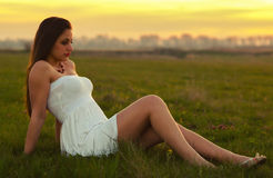 Beautiful girl sitting on the meadow Stock Image