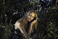 Beautiful girl is sitting in nature in the evening Stock Images