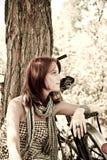 Beautiful girl sitting near bike.. Beautiful girl sitting near bike and tree at rest in forest. Photo in retro style Stock Photography