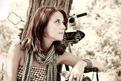 Beautiful girl sitting near bike.. Beautiful girl sitting near bike and tree at rest in forest. Photo in retro style Royalty Free Stock Photography