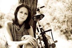 Beautiful girl sitting near bike.. Beautiful girl sitting near bike and tree at rest in forest. Photo in retro style Royalty Free Stock Photo