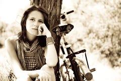 Beautiful girl sitting near bike.. Beautiful girl sitting near bike and tree at rest in forest. Photo in retro style Stock Photos