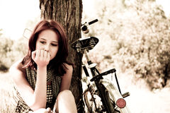 Beautiful girl sitting near bike.. Beautiful girl sitting near bike and tree at rest in forest. Photo in retro style Royalty Free Stock Image