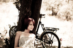 Beautiful girl sitting near bike.. Beautiful girl near bike and tree at rest in forest. Photo in retro style Stock Photography