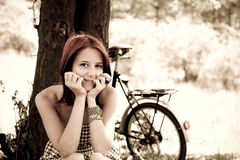 Beautiful girl sitting near bike. Royalty Free Stock Images