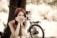 Beautiful girl sitting near bike. Beautiful girl sitting near bike and tree at rest in forest. Photo in retro style Royalty Free Stock Images