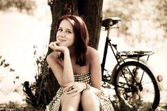 Beautiful girl sitting near bike. Beautiful girl sitting near bike and tree at rest in forest. Photo in retro style Stock Images