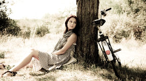 Beautiful girl sitting near bike.  Stock Photo