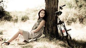 Beautiful girl sitting near bike.. Beautiful girl sitting near bike and tree at rest in forest. Photo in retro style Stock Photo