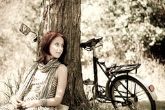 Beautiful girl sitting near bike. Photo in retro s. Beautiful girl sitting near bike and tree at rest in forest. Photo in retro style Stock Images