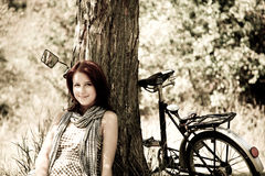 Beautiful girl sitting near bike. Photo in retro s. Beautiful girl sitting near bike and tree at rest in forest. Photo in retro style Royalty Free Stock Photo