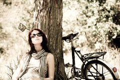 Beautiful girl sitting near bike. Photo in retro s. Beautiful girl sitting near bike and tree at rest in forest. Photo in retro style Royalty Free Stock Photography