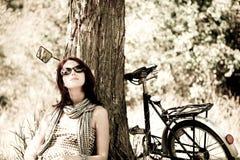 Beautiful girl sitting near bike. Photo in retro s Royalty Free Stock Photography