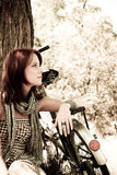 Beautiful girl sitting near bike. Photo in retro s. Beautiful girl sitting near bike and tree at rest in forest. Photo in retro style Royalty Free Stock Images