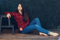 Beautiful girl sitting near the chair. In the Studio Royalty Free Stock Photo