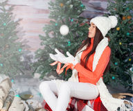 Beautiful girl sitting  near  Christmas tree Royalty Free Stock Images