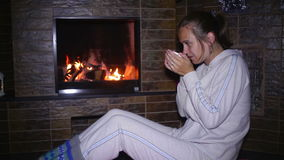 Beautiful girl sitting near the fireplace and drinking tea stock footage
