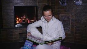 Beautiful girl sitting near the fireplace and watching photo album stock video