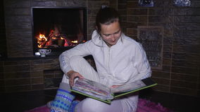 Beautiful girl sitting near the fireplace and watching photo album stock video footage