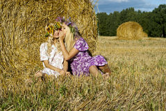 Beautiful girl sitting near the haystacks Royalty Free Stock Photos