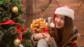 Beautiful girl sitting near New Year tree with a present Royalty Free Stock Photography