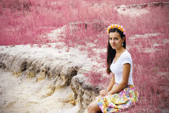 Beautiful girl is sitting near pink flowers field Stock Photo