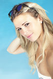 Beautiful blonde hair girl sitting near the pool in swimsuit. Summer concept. Beautiful girl sitting by the pool in a swimsuit. A beautiful young blonde girl is Royalty Free Stock Photo