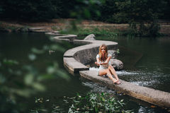 Beautiful girl sitting near the water and Stock Images