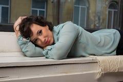 Beautiful girl sitting near window pane Royalty Free Stock Image