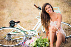 Beautiful Girl Sitting Next to Bike Stock Image