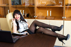 Beautiful girl sitting in an office at a desk Stock Photos