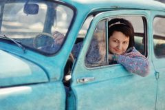 Girl and vintage car. Beautiful girl sitting in an old car and smiling with pleasure stock images