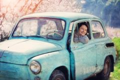 Girl and vintage car. Beautiful girl sitting in an old car and smiling with pleasure royalty free stock photo