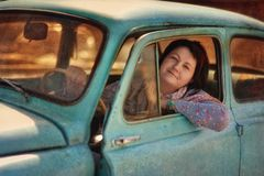Girl and vintage car. Beautiful girl sitting in an old car and smiling with pleasure royalty free stock image