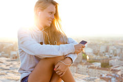 Beautiful Girl Sitting On The Roof And Listening To Music. Stock Images