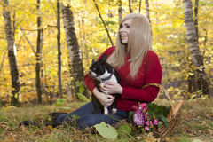 Beautiful girl sitting outdoors in autumn with her Boston Terrie Stock Photos