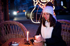 Beautiful girl sitting outdoors in winter with a cup and a candl Royalty Free Stock Images