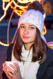 Beautiful girl sitting outdoors in winter with a cup Stock Images