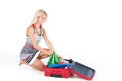 Beautiful girl sitting and packing luggage. Royalty Free Stock Photos